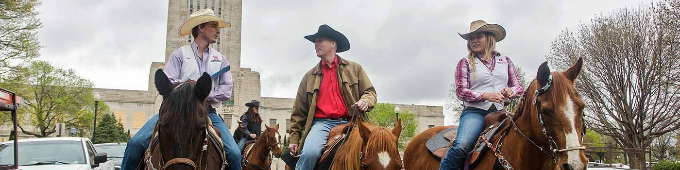 Governor Ricketts riding a horse in front of the Capital