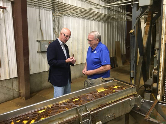 Governor Ricketts examines one of the pellets made by Nebraska Distillers Products at the company's Ord plant during a tour with co-owner and production manager Gaylord Boilesen.