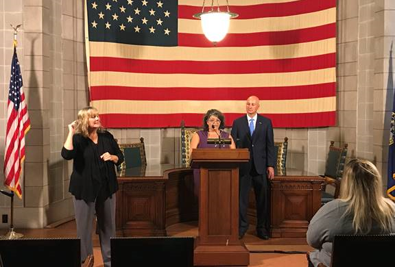 State teammate April Claussen relates her experience with SNAP Next Step  as Gov. Ricketts looks on during this afternoon's press conference.
