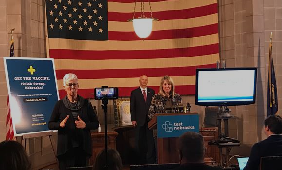 Sarah Sortum (podium) of Switzer Ranch and Gov. Ricketts (in back of podium)  at today's Leopold Conservation Award ceremony at the State Capitol.